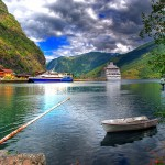 Fjordarm med robåt i forgrunnen. To skip på fjorden.