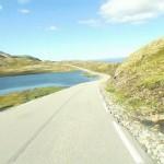 Fjellvei i flatt terreng. En liten innsjø.