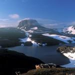 Fjell med snø og en liten innsjø.