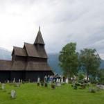 Mørkebrun kirke med kirkegård i forkant.