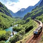 Bratt dal med grønne trær, elv og et tog som snirkler seg frem.